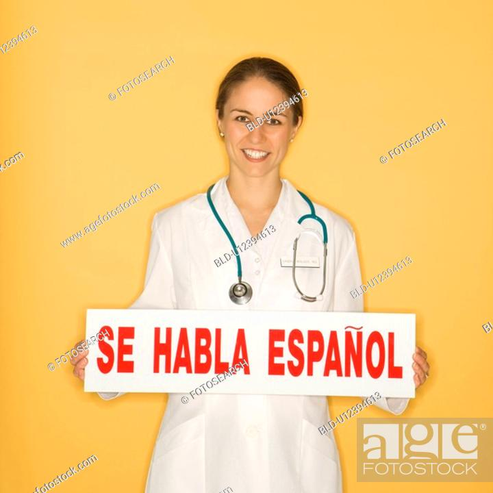 Stock Photo: Portrait of doctor holding up se habla espanol sign against yellow background.