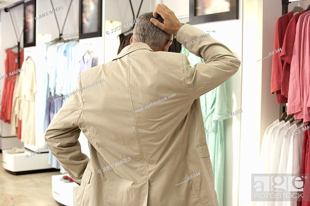 Stock Photo: Mature man shopping in clothes shop, scratching head, hand on hip, rear view.
