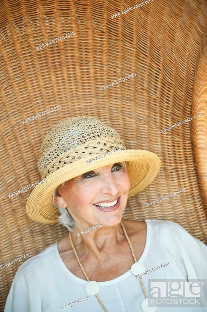 Stock Photo: Germany, Bavaria, Senior woman sitting on wicker chair, smiling.