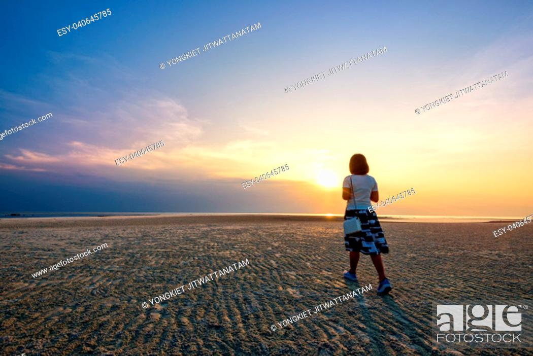 Imagen: Young woman tourist strolling on the beach watching the beautiful natural landscape, colorful of the sky and the sea during a sunset at Nathon Sunset Viewpoint.