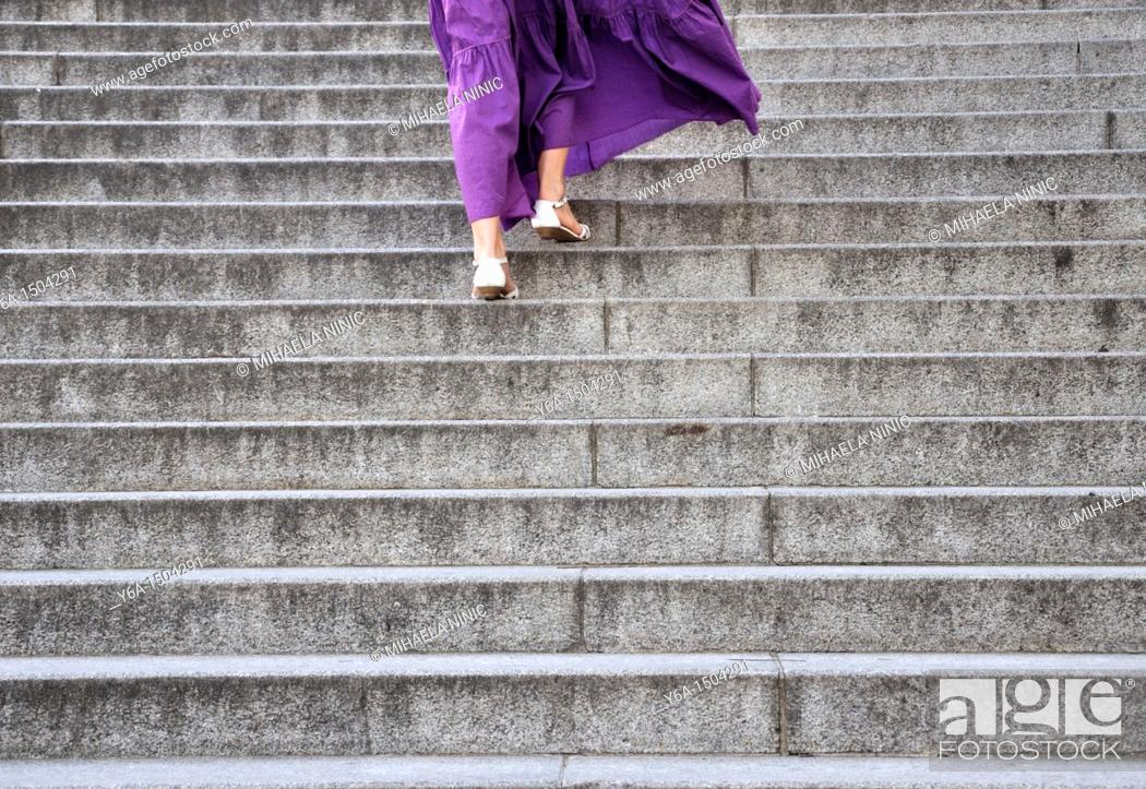 Stock Photo: Young woman walking up staircase outdoors rear view.