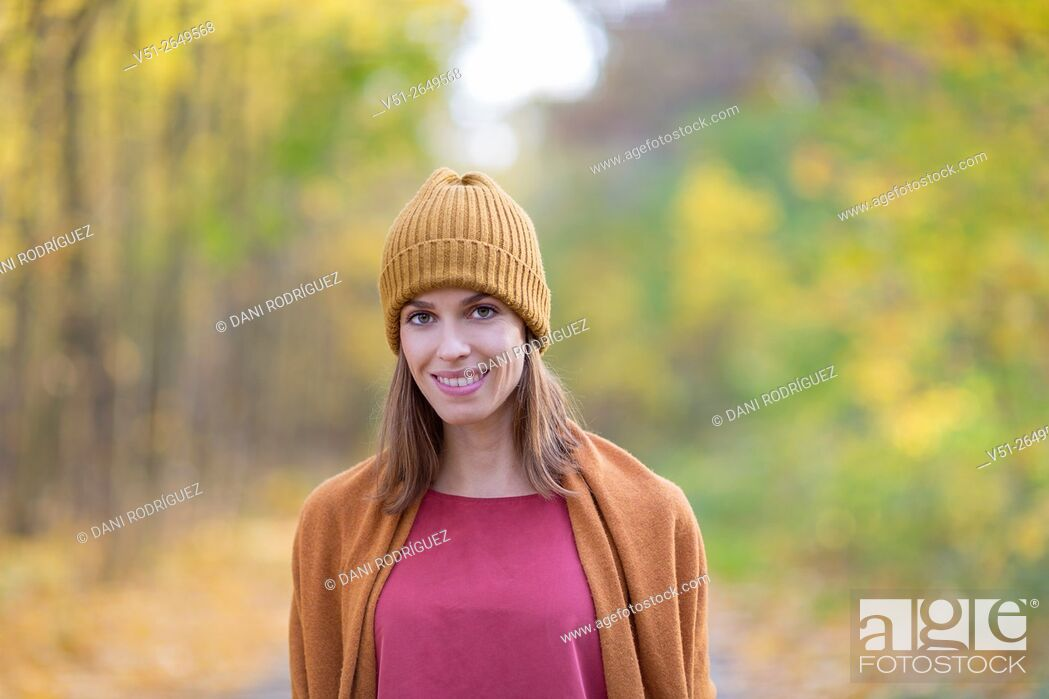 Stock Photo: Brunette Woman in Park in Autumnn smiling at camera.