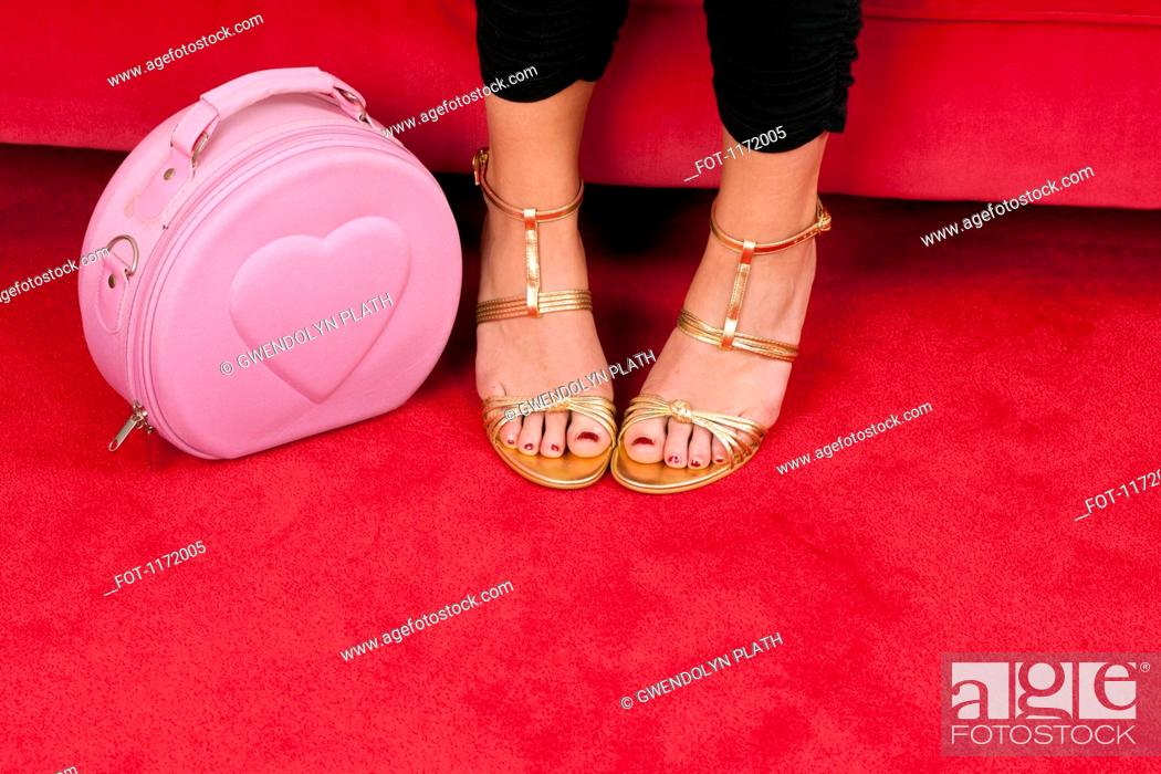 Stock Photo: A woman wearing gold strappy heels focus on feet next to a pink purse.
