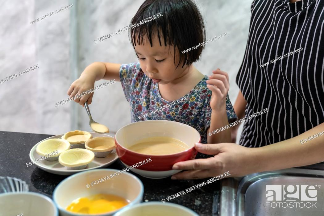 Stock Photo: Asian girl cooking egg tart bakery with her mom, housework for child make executive function for kid. Houseworking food lifstyle and family concept.