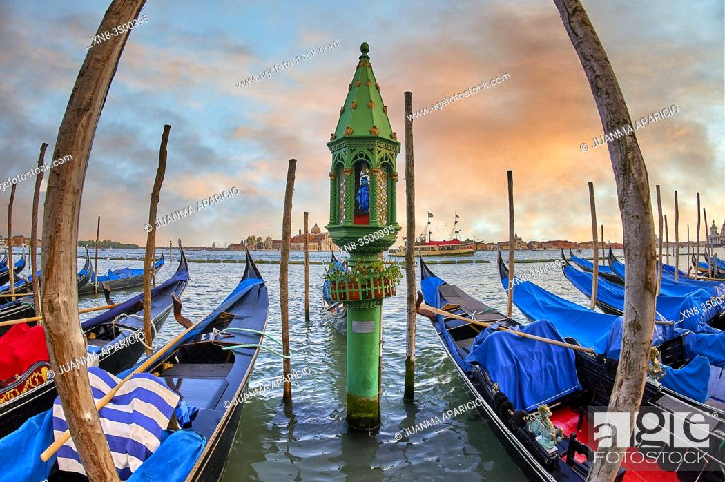 Stock Photo: Sunset view of gondolas at St Mark's Square with the island of San Giorgio Maggiore behind , with its church front designed by Andrea Palladio and begun in 1566.