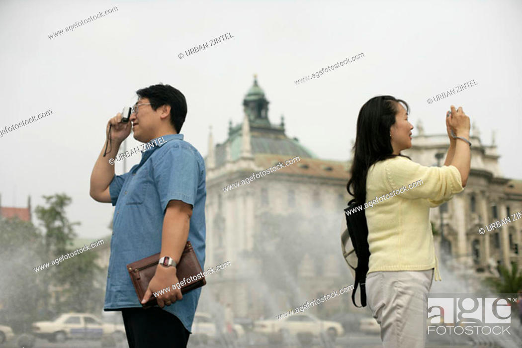 Stock Photo: Heterosexual Asian couple taking pictures in front of a fountain.