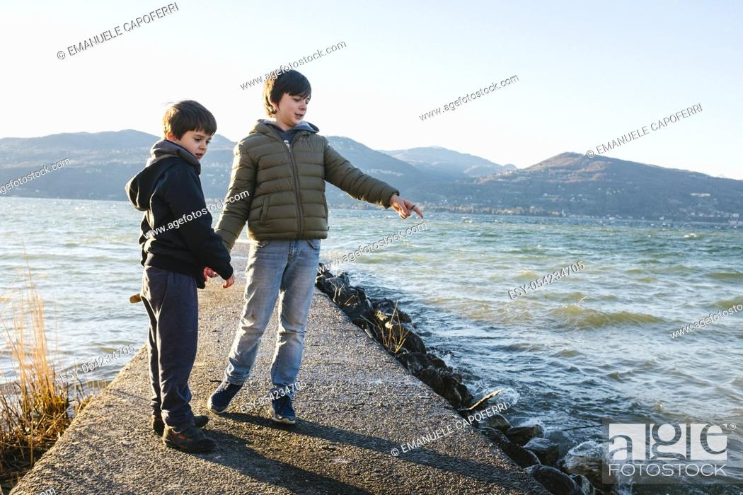 Imagen: brothers children on the pier in the beach of Lake Maggiore.