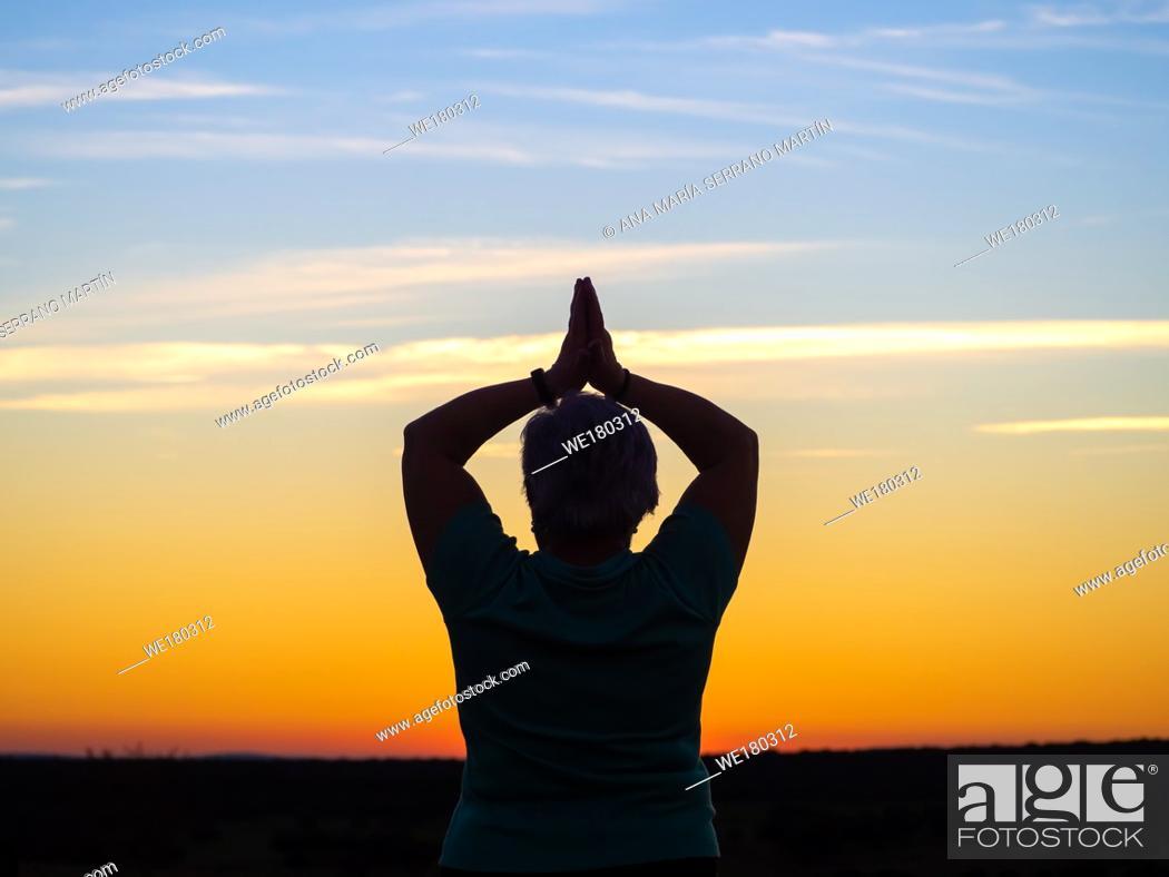 Imagen: A senior woman practicing yoga at sunset.