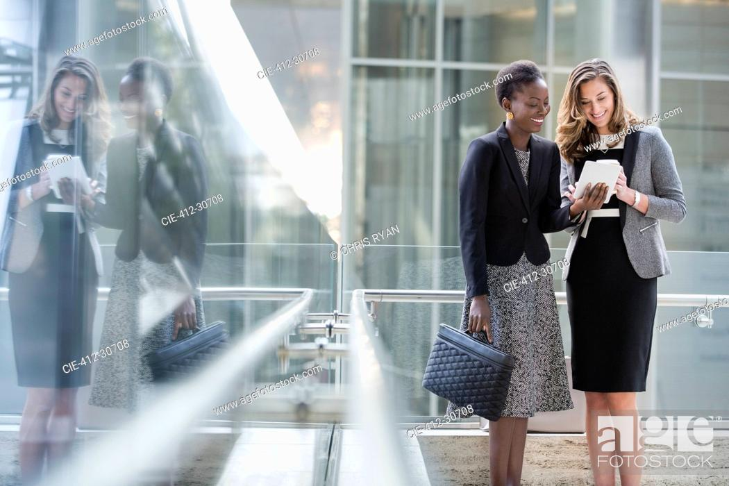 Stock Photo: Corporate businesswomen using digital tablet.