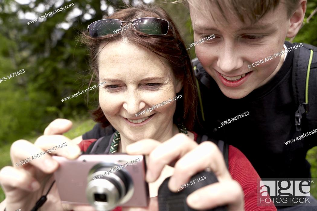 Stock Photo: Mature woman and teenager son in the countryside, with digital camera. Bad Tölz, Upper bavaria, Germany.