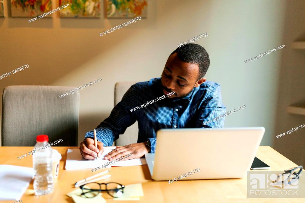 Stock Photo: Young man at table with laptop writing in notebook.