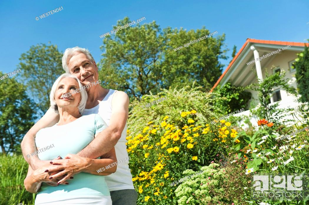 Stock Photo: Germany, Bavaria, Man and woman embracing each other in garden, smiling.