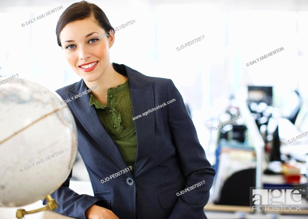 Stock Photo: Smiling businesswoman next to globe in office.
