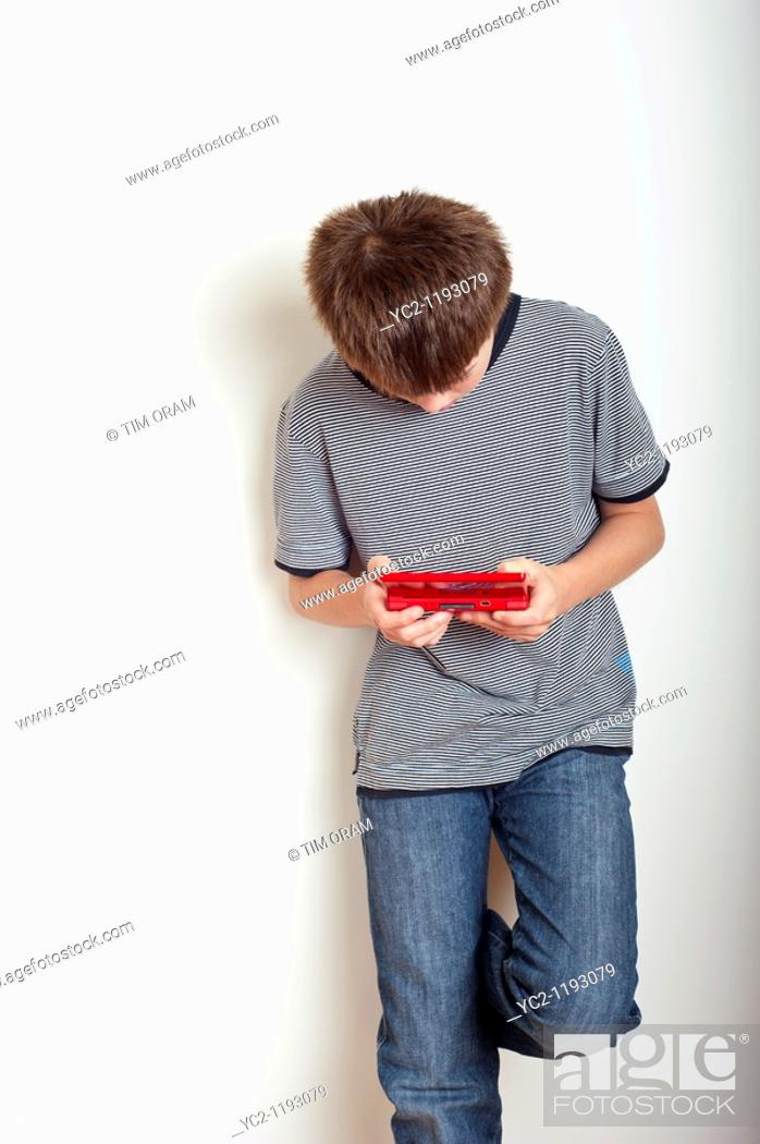 Stock Photo: 10 year old boy playing with a Nintendo DS handheld games console in the studio.