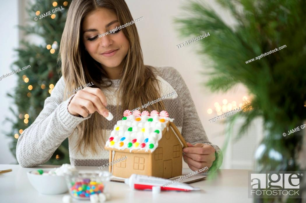 Stock Photo: Young woman preparing gingerbread house.