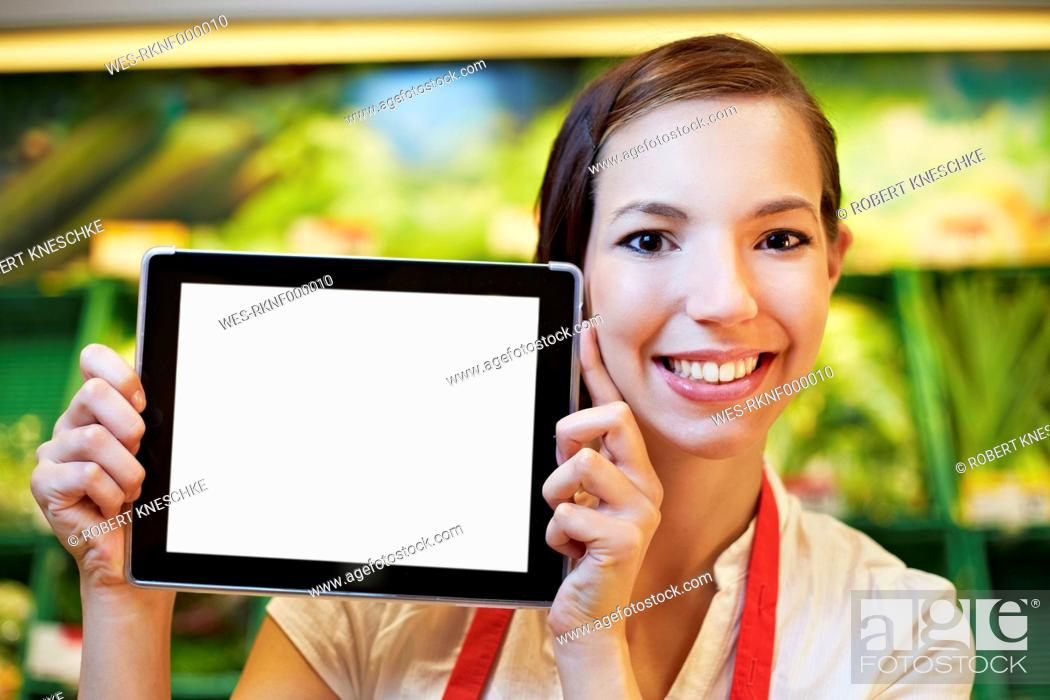 Stock Photo: Germany, Cologne, Young woman with digital table in supermarket.