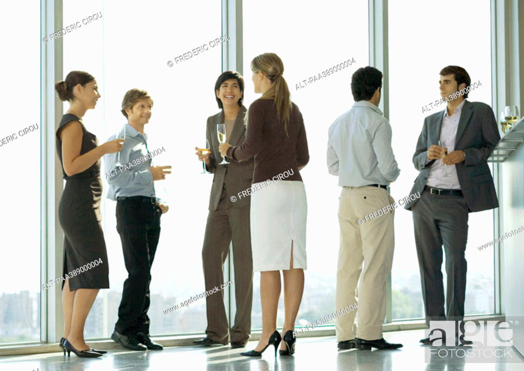 Stock Photo: People standing with glasses during office party.