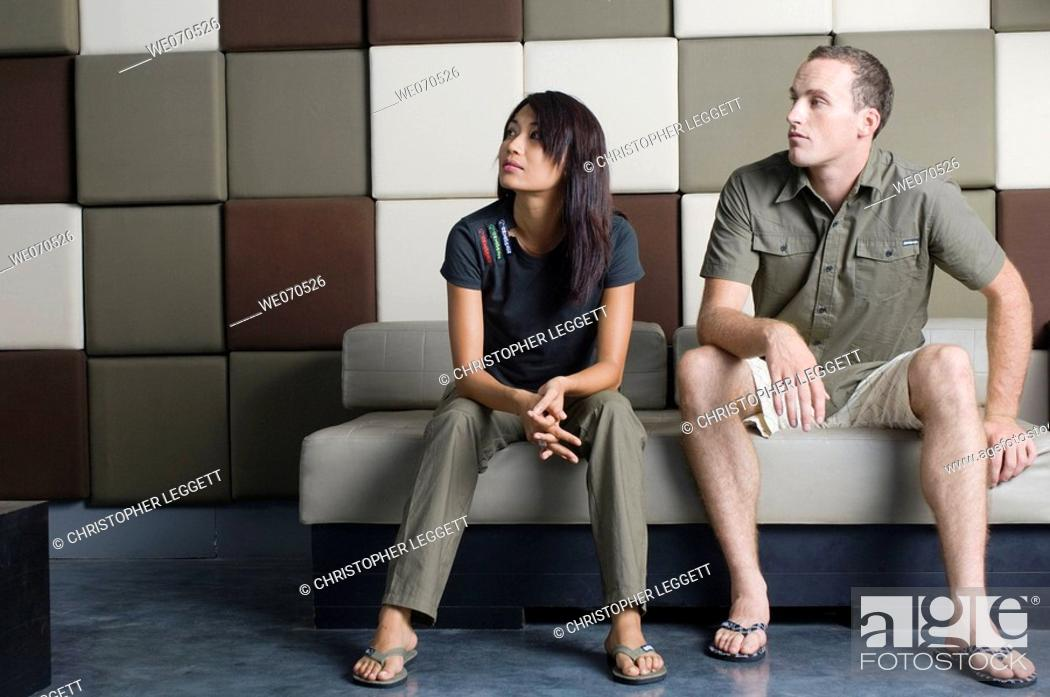Stock Photo: Young couple sitting and relaxing on couch.
