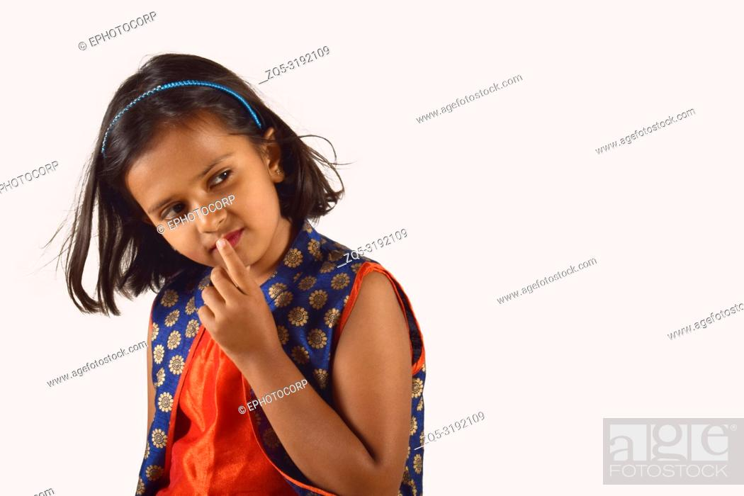 Imagen: Little girl posing in front of camera with finger on lip in thinking pose. Pune, Maharashtra.