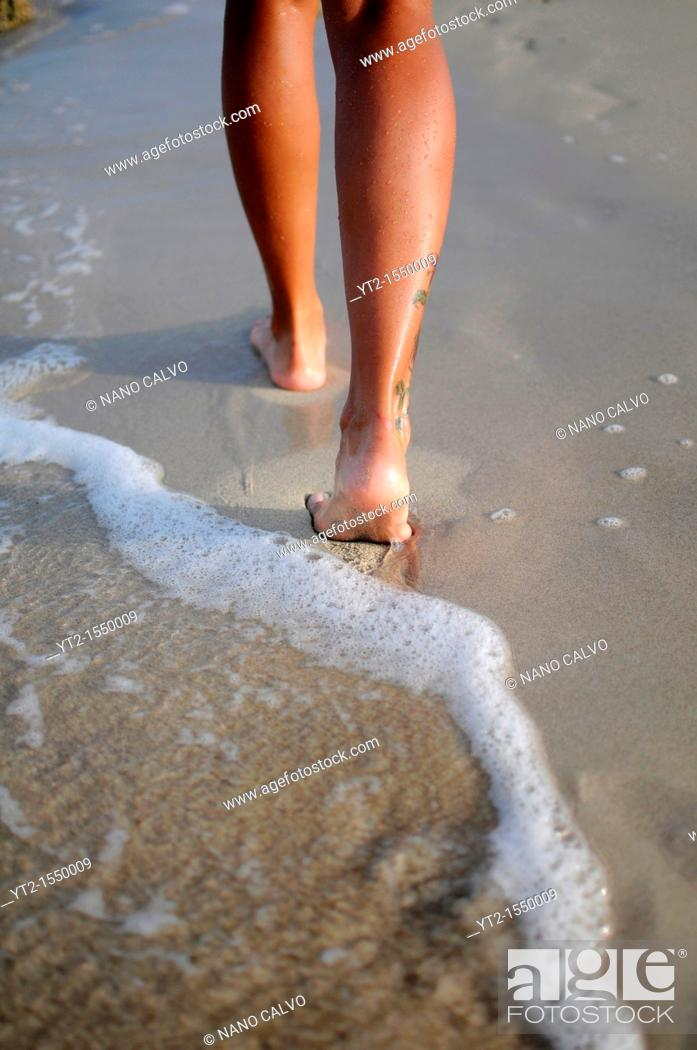Stock Photo: Legs of young woman walking on the beach.