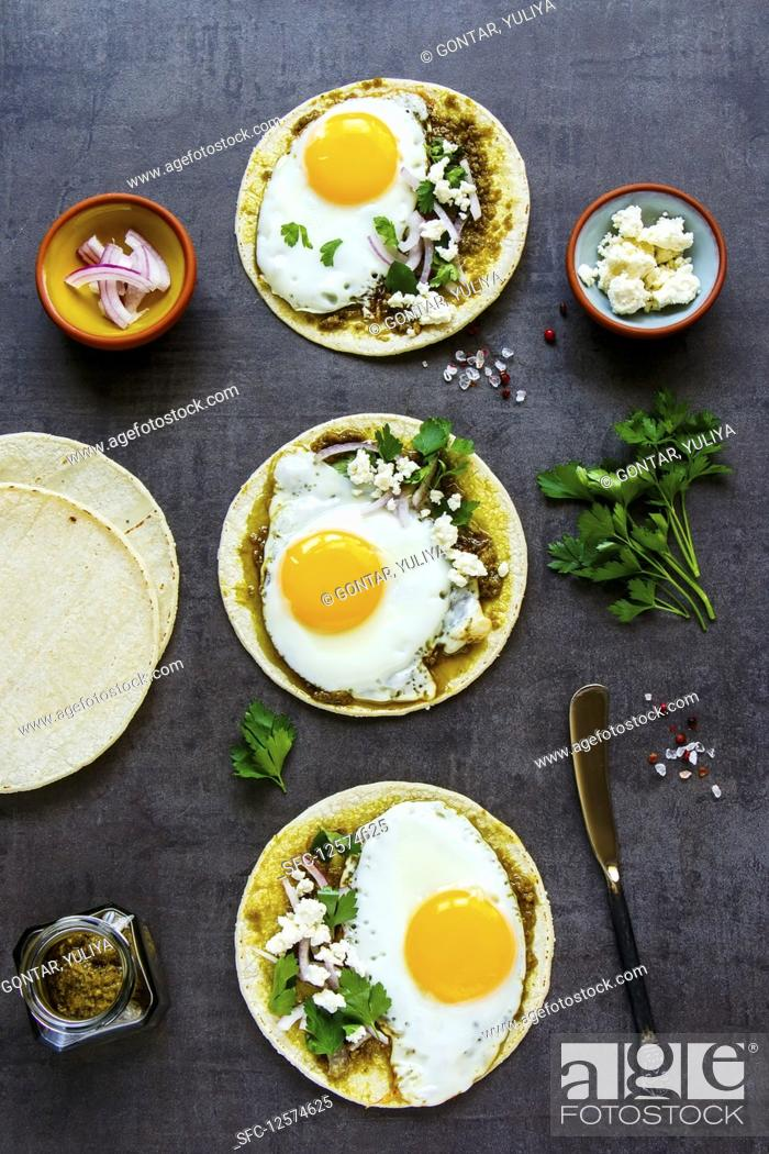 Stock Photo: Corn tortillas with fried eggs, pesto sauce and feta cheese.
