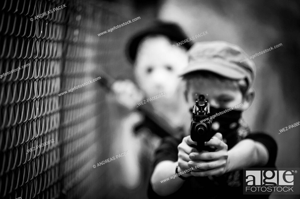 Imagen: Masked boy aiming with toy gun.