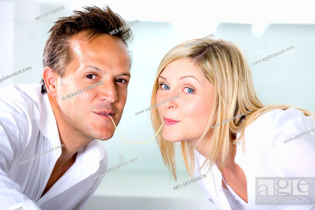 Stock Photo: Germany, Mid adult couple eating noodles.