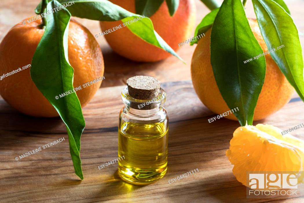 Stock Photo: A bottle of tangerine essential oil on a wooden table, with whole tangerines and tangerine wedges in the background.