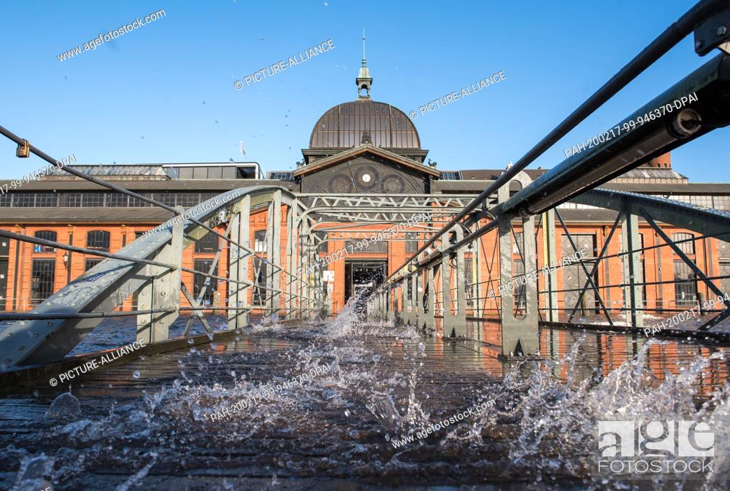 Stock Photo: 17 February 2020, Hamburg: Water splashes during a storm tide at the ferry pier at the fish market on the Elbe in front of the fish auction hall.