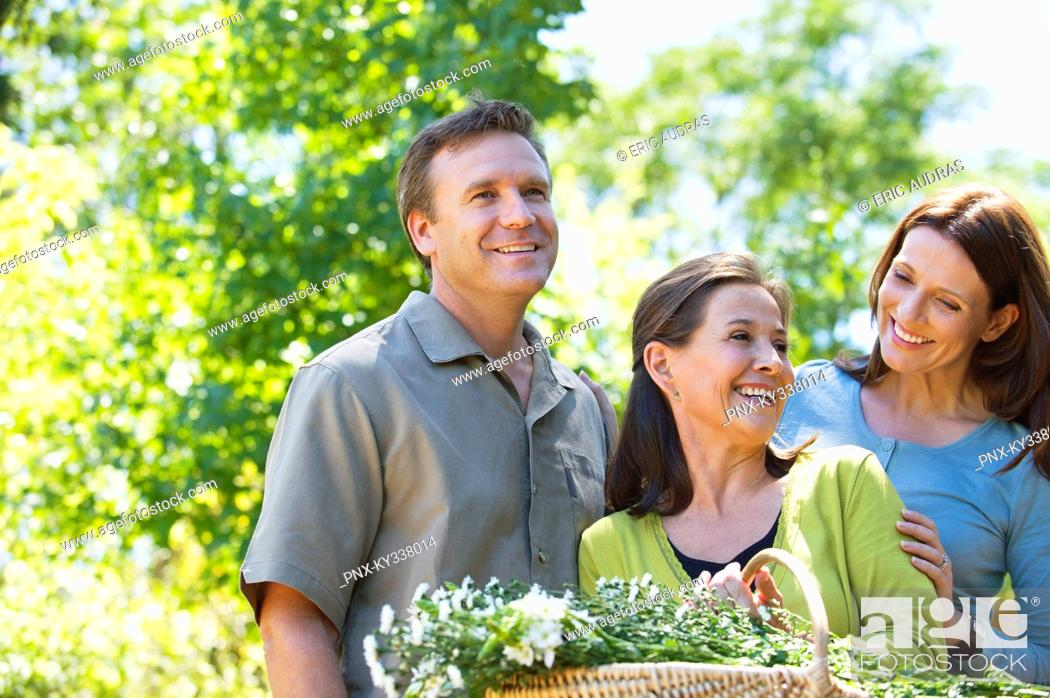 Stock Photo: Woman standing with his son and daughter in law while holding basket of flowers.