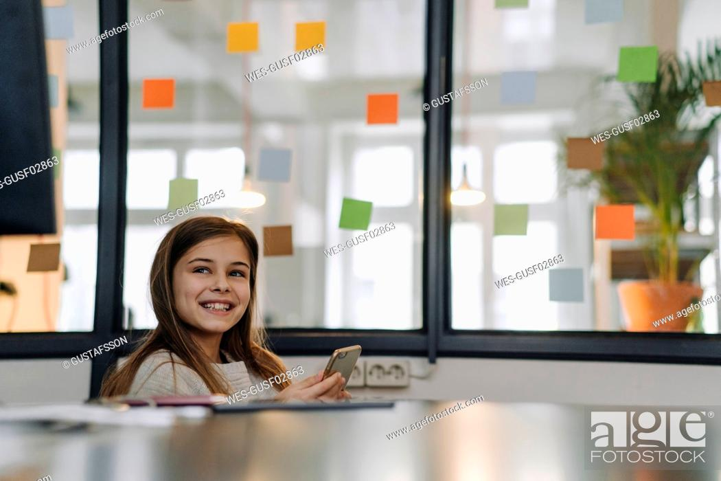 Stock Photo: Happy girl with smartphone at desk in office.