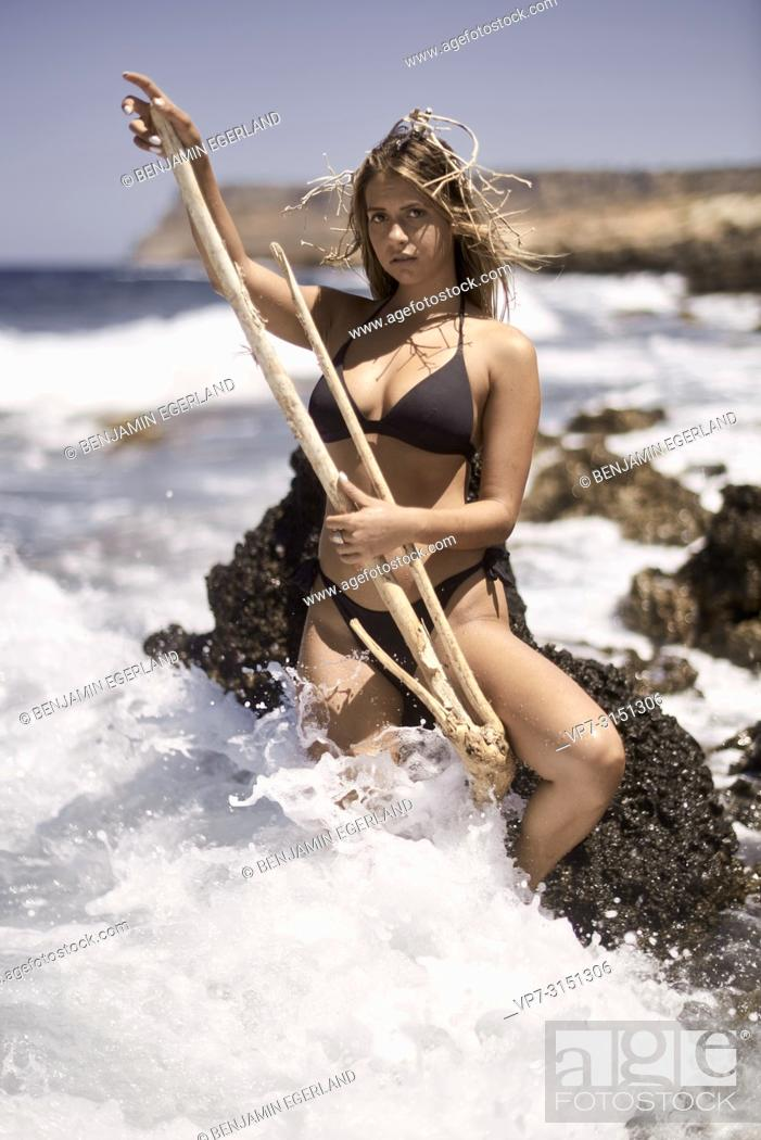 Stock Photo: Sensual woman with wood stick and wooden coronal at seaside, Sissi, Crete, Greece.