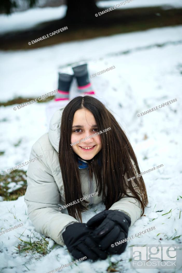 Imagen: portrait of an 11-year-old girl outside under a snowfall, in a forest, dressed in a down jacket, a windbreaker.