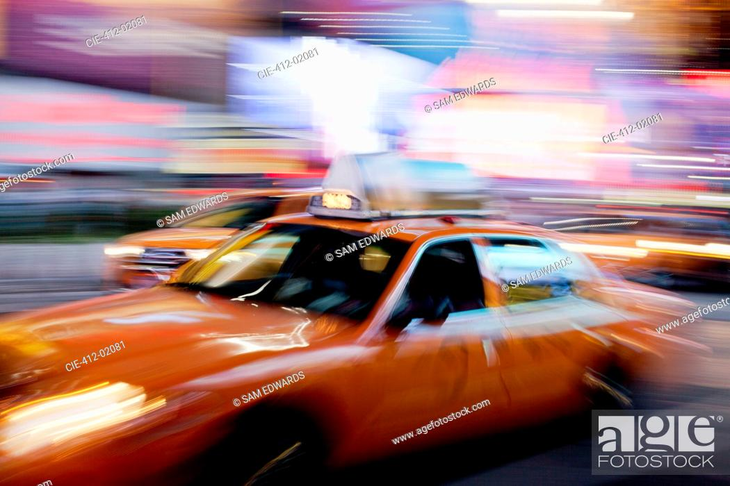 Stock Photo: Blurred view of taxi on city street at night.