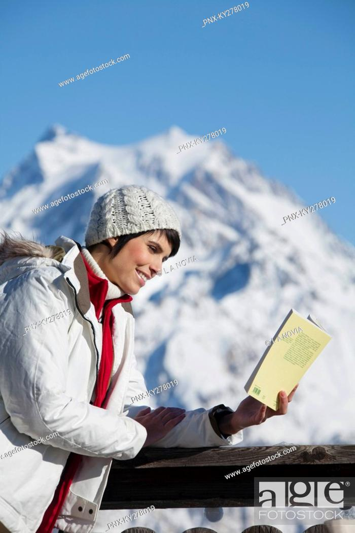 Stock Photo: Young woman reading a book, enjoying winter sun, mountains in background.