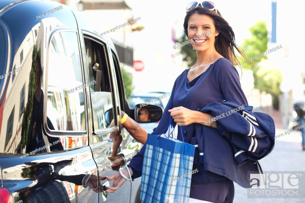 Stock Photo: Portrait of a beautiful woman standing by the car.