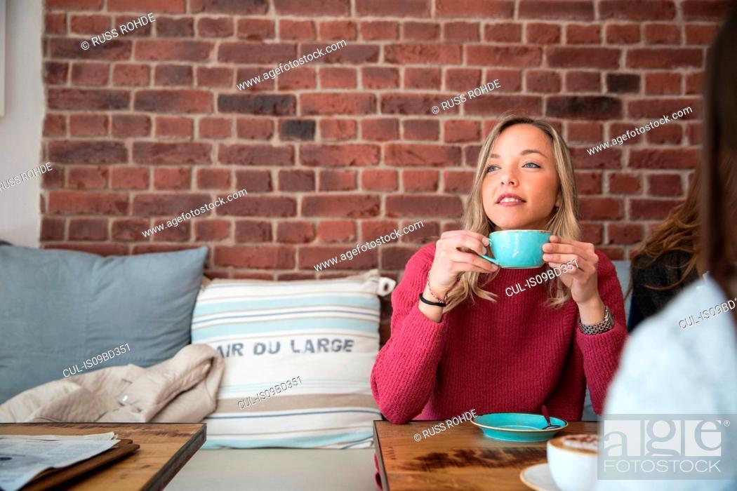 Imagen: Two female friends sitting in cafe, drinking coffee.