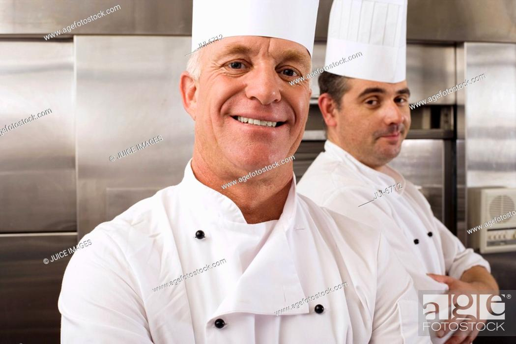Stock Photo: Two male chefs standing in commercial kitchen, arms folded, smiling, close-up, portrait.