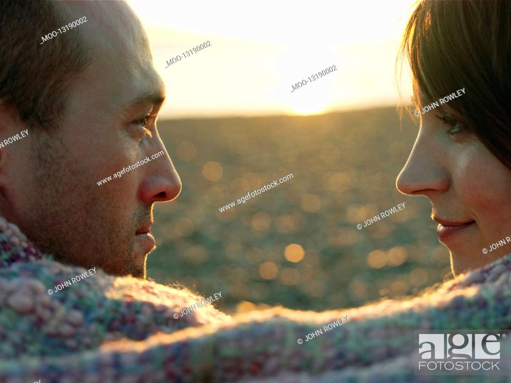 Stock Photo: Couple face to face wrapped in blanket on beach close up.