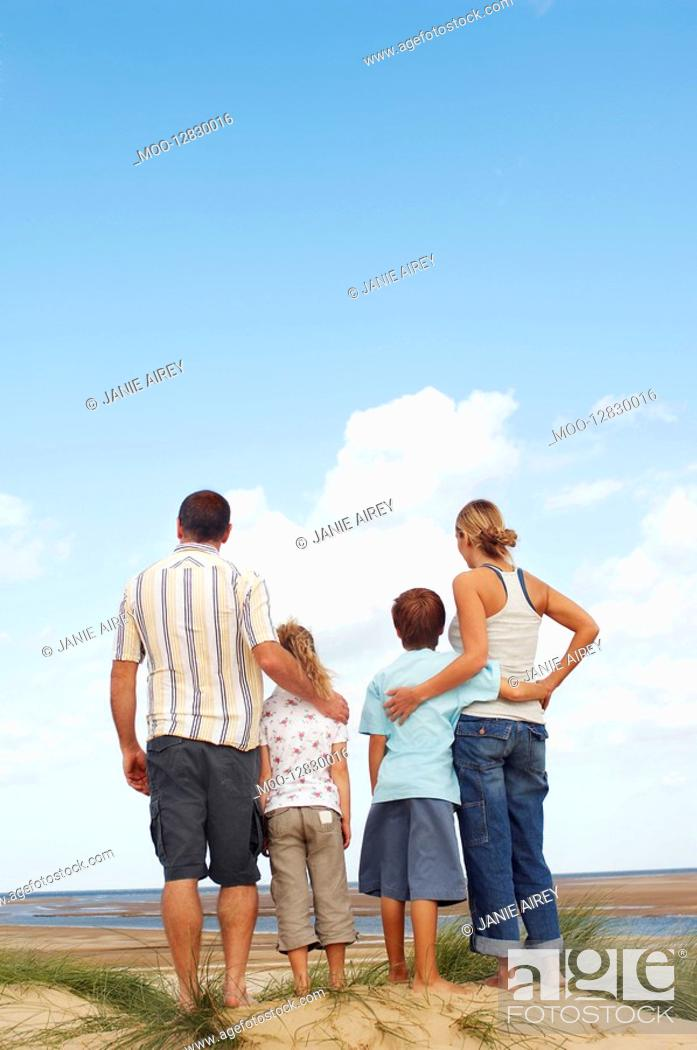 Stock Photo: Family standing on sand dune on beach looking at view back view.