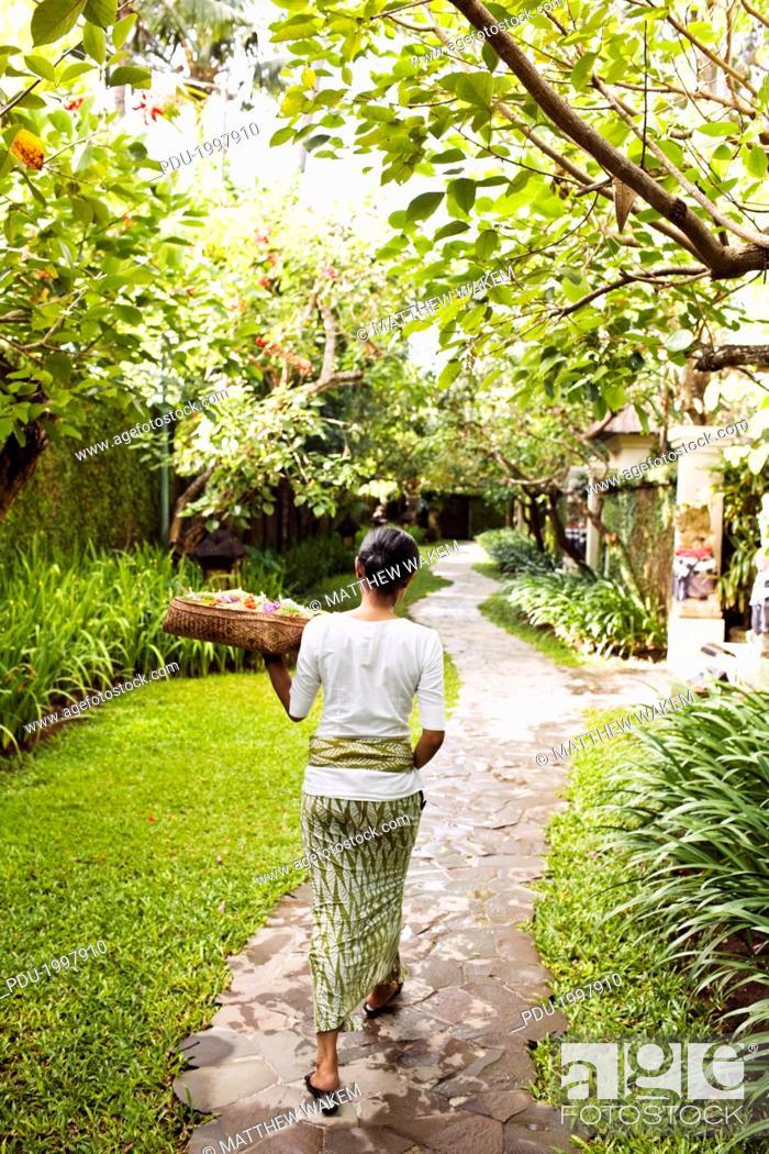 Stock Photo: Balinese woman makes morning offerings at Kayumani.