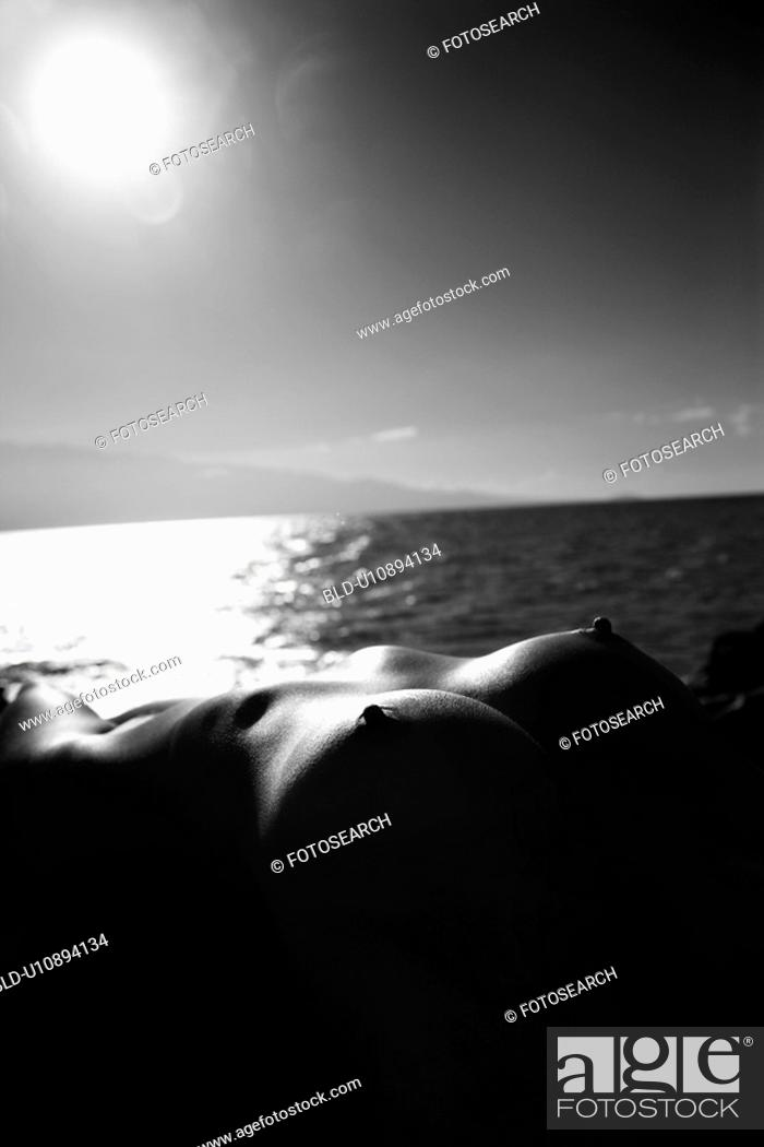 Stock Photo: Close up of Filipino young nude woman lying on back against ocean and sun in sky.