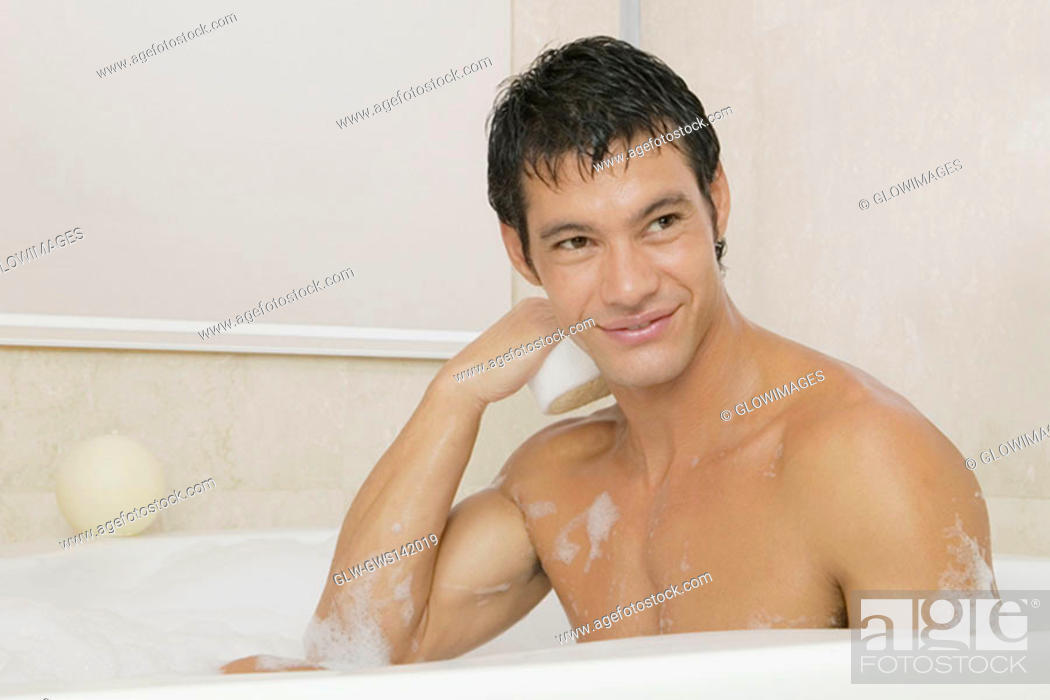 Stock Photo: Mid adult man sitting in a bubble bath.