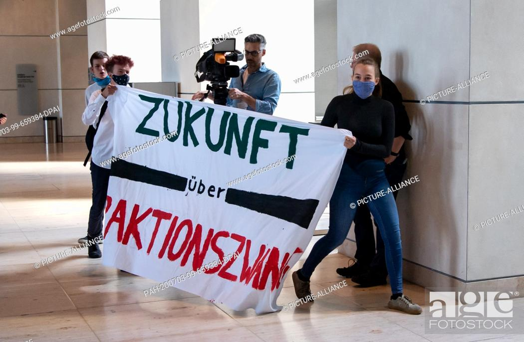 """Stock Photo: 03 July 2020, Berlin: During the plenary session in the German Bundestag, young activists hold a banner with the inscription """"""""Zukunft über Fraktionszwang""""""""."""