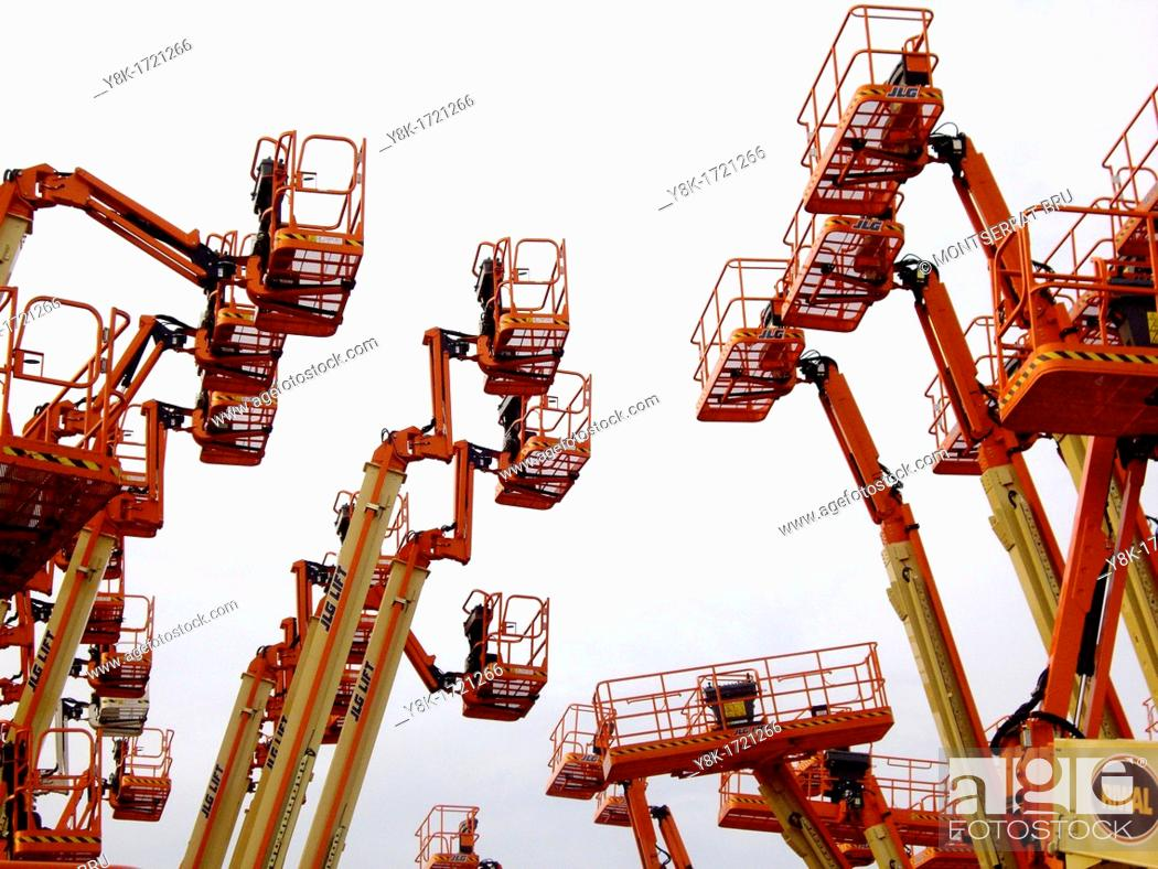 Stock Photo: Industrial aerial work platforms facing eachother like getting into a clash against white background in Dordrecht, Zuid Holland, The Netherlands.