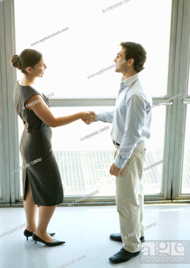 Stock Photo: Businessman and businesswoman shaking hands, full length.