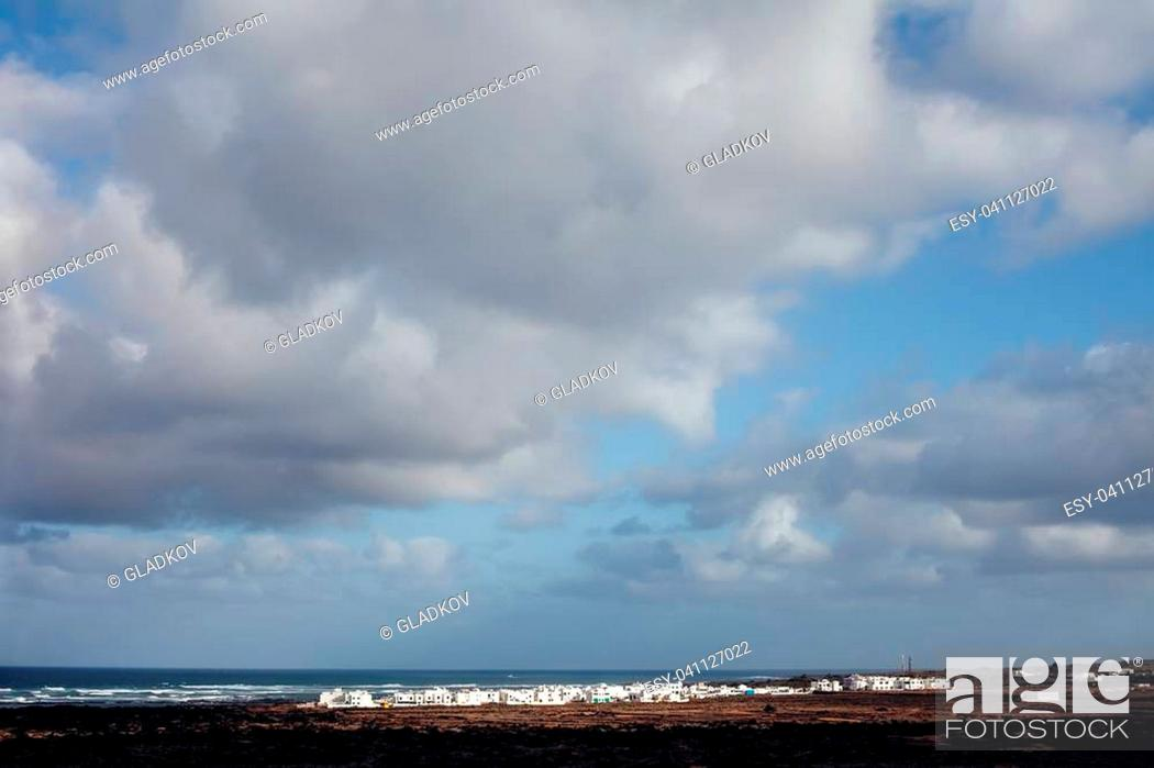 Stock Photo: Dramatic sky over ocean and city in Lanzarote island. Travel destination.