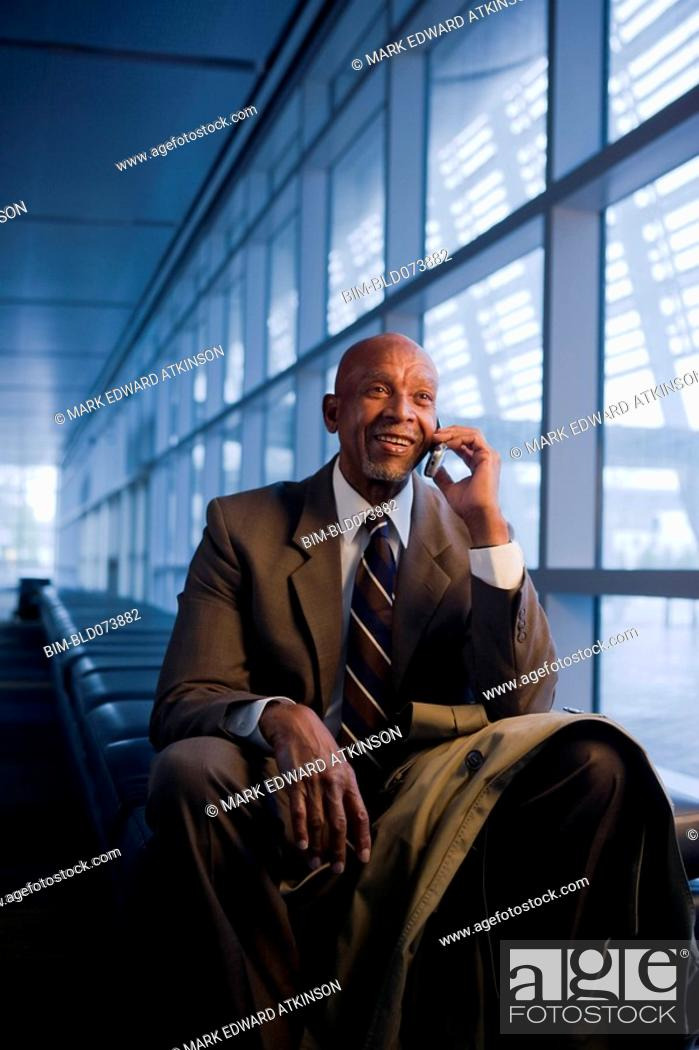 Stock Photo: African businessman using cell phone.
