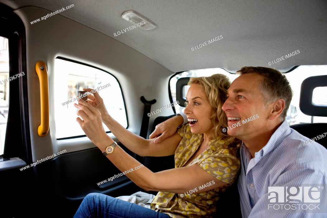 Stock Photo: A middle-aged couple in a London taxi, taking a photograph.