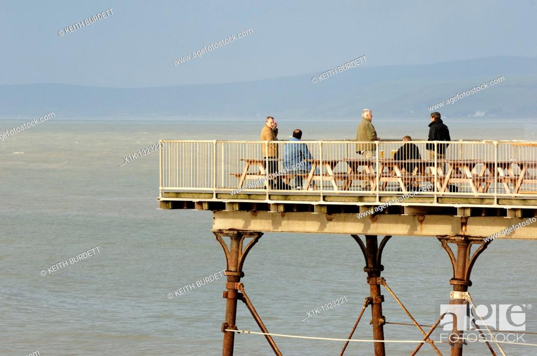 Stock Photo: Middle aged men drinking pints of lager at the end of Aberystwyth Pier, Wales.